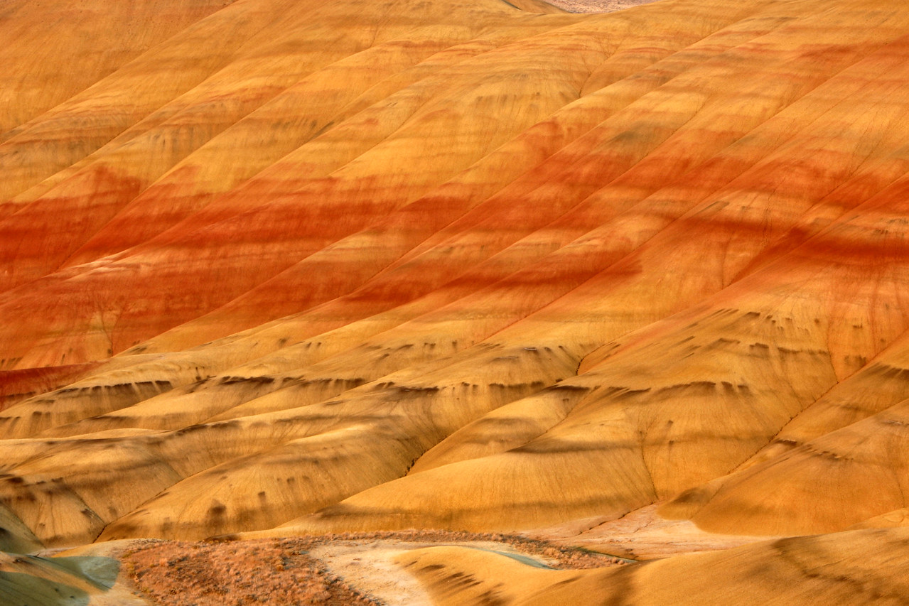 """A closeup of the Painted Hills at sunset. The texture and bands of colors from these 30 million year old hills were mesmerizing. While taking pictures, we broke out the traditional bottle of champagne and enjoyed the final hour of daylight. After the sunset, we drove 3 miles up the road to the very, very small town of Mitchell, Oregon. We didn't expect to find much open, but soon found ourselves in the middle of the annual """"Painted Hills Festival"""". We grabbed a quick dinner, walked around a bit, and then turned back up the road to camp for the night. <br /> <br /> <br /> <a href=""""http://www.paintedhillsfestival.homestead.com/"""">http://www.paintedhillsfestival.homestead.com/</a>"""