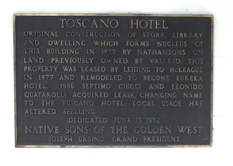 """Toscano Hotel, Sonoma, 2021.                                           The Toscano Hotel was built in the early 1850s and was initially used as a general store and lending library. The name Toscano Hotel was adopted in 1886 when Settimo Ciucci and his business partner Leonido Quartaroli turned it into a workingman's hotel and bar. Guests included Italian quarry workers who quarried basalt blocks from the hills north of the Sonoma Plaza, railroad workers, vineyard workers, and eventually vacationing families from the greater Bay Area (who would come to visit the hot springs). The accommodations were simple, never fancy. The kitchen/dining room was added in 1902 and offered """"fine Italian food."""" After being operated for nearly 70 years (1886 – 1955) by two generations of the Ciucci family, it was sold to the California Department of Parks and Recreation in 1957. Today, visitors to the hotel can view period furnishings and kitchenware as well as historical photographs of the hotel, its guests, and the Ciucci family."""