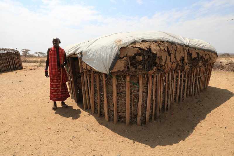 The chieftain of the Samburu village is standing proudly in front of the hut that he shares with his wife. The tradition is that men build the basic structure and women do the rest to turn it into a home. Men can marry as many women as they want (or can afford) but each woman gets her own hut. The men would then set up a schedule of when they would stay with each one. This chieftain said he had only one wife but his brother has three.  Photo by Leah Bensen