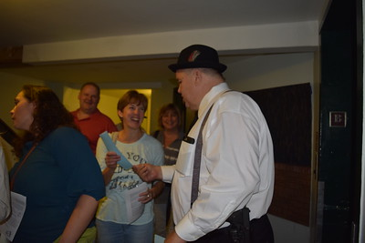 Cops & Doughnuts President Greg Rynearson, playing a Prohibition-era police officer, hands out tickets for criminal activity at the Clare County Arts Council Roaring Twenties Speakeasy fund raiser at the Doherty Hotel.