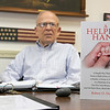 "Robert Doucette with his book ""A Helping Hand"" in his office in Leominster Friday, August 23, 2019. SENTINEL & ENTERPRISE/JOHN LOVE"