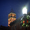 The tower of the former fire station at Middle and Shattuck streets in Lowell stands amid a snowy Friday evening behind a decorated wreath on Middle Street.