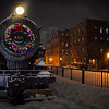 A wreath decorates the Boston & Maine Railroad engine that sits in downtown Lowell on Friday evening as a light snow falls.