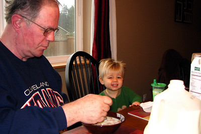 zach uses his cuteness to score some cereal from grandpa