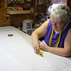 Kathy Cutting Out the Satin that has the Sparkles on It.<br />  Kathy got the muslin coat as she wanted it then took it apart using the chain stitch she had it sewn with and made the pattern from the pellon. Then she has it laid onto the satin to cut around.