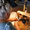 """Sewing the Side Piece Onto the Front of the Dress.       For """"Work""""<br /> My wife, Kathy, sewing up a satin wedding dress for a friends daughter. The outfit will also have a long coat of white satin, with tiny, shinny, silver flecks on the satin, to wear over the dress."""