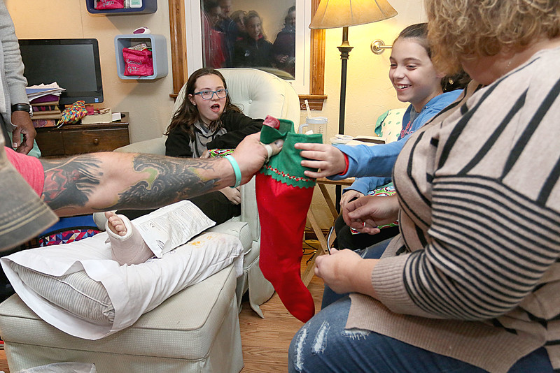"Dave Mansfield and Rob Ollivierra are making Christmas brighter for a few local families by helping them out with furniture, cleaning out their homes, delivering toys, and more. It's their ""Christmas Miracle."" McKenna Boisvert, 11, her sister Mallory Boisvert, 9, and mom Shelby Boisvert are given Christmas gifts at their home on Thursday night. SUN/JOHN LOVE"