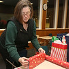 "Dave Mansfield and Rob Ollivierra are making Christmas brighter for a few local families by helping them out with furniture, cleaning out their homes, delivering toys, and more. It's their ""Christmas Miracle."" At the Community Christian Fellowship in Lowell Janet Surprenant helped wrap the gifts they where going to give out. SUN/JOHN LOVE"