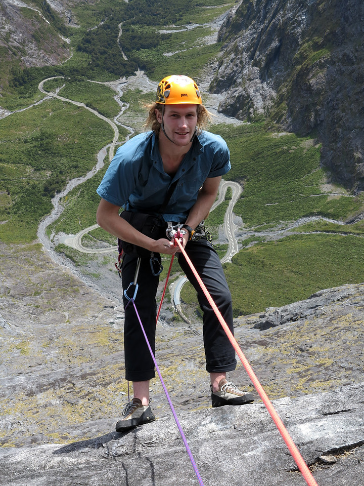 Pete abseiling with the Cleddau Portal of the Homer Tunnel between his legs