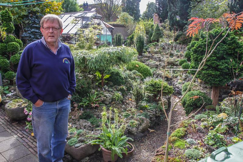 Geert in his rock garden with greenhouse