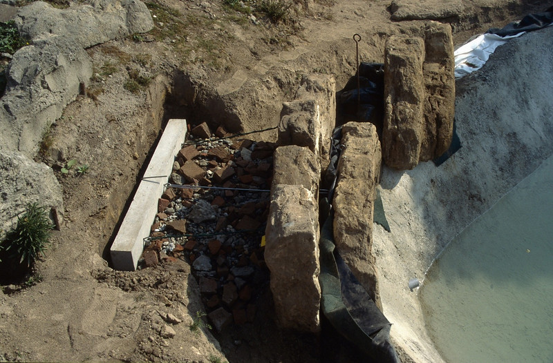 phase 10, finishing touch of the pond edge with concrete anchor and tufa rocks (construction rockgarden 1992)