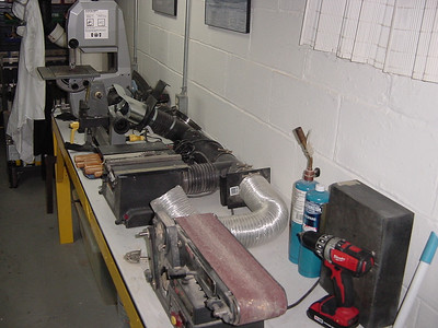 """Power bench.. up front is the tool of mass destruction (belt sander) bench top table saw, 12"""" wood lathe and band saw."""