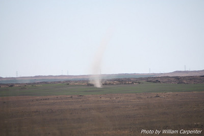 A dust devil visible in the distance.