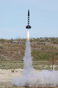 "A rocket named ""Harlequin"" lifts off from the high-power pads."