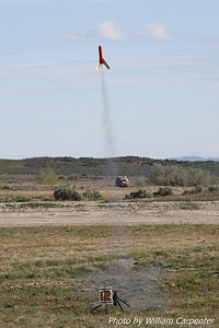 A Madcow Rocketry Mozzie lifts off from the mid-power pads.