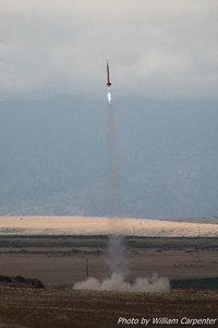 A rocket launches from the away cell on an L-impulse Blue Thunder motor.