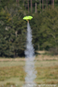 An Estes Snitch lifts off from the model pads.
