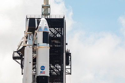 Close-up of the Crew Dragon spacecraft atop the Falcon 9 rocket featuring the NASA meatball and United States flag.