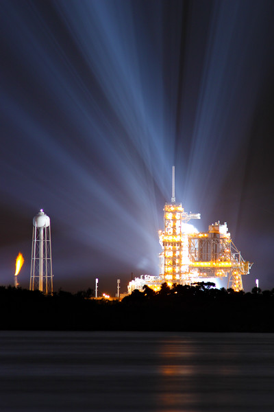 This is LC39A, the only pad left for the shuttle program. Behind the tower sits the shuttle stack with <i>Discovery</i>. Powerful xenon lights illuminate the pad and can be seen for miles. To the left of the pad stands the 300,000 gallon water tower for the Sound Suppression System, which releases just before the engines ignite. The system prevents the shuttle from being damaged by its own Earth-rattling sound.