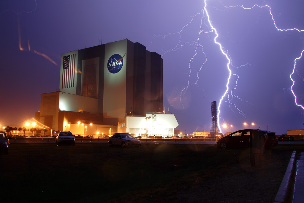 Thursday, April 28 - Lightning strikes near Kennedy Space Center with the Vehicle Assembly Building in the foreground.