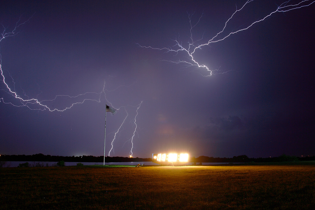 Thursday, April 28 - Lightning strikes near Kennedy Space Center with the Press Site Countdown Clock and Flag Pole in the foreground.