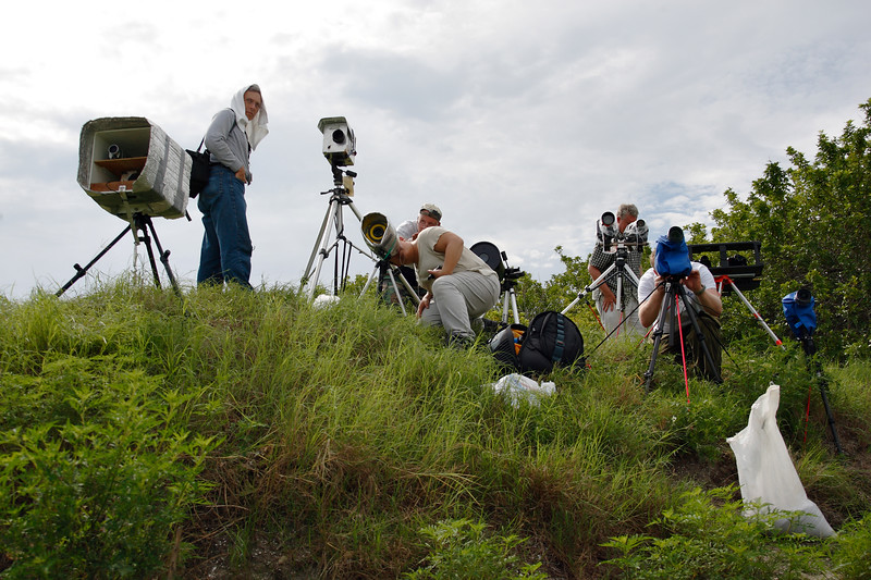 """Photographers set up and check equipment on one of several """"camera mounds"""" located just outside the launch pad's perimeter fence. Each setup is unique, designed to survive in the elements and trigger automatically at the time of launch."""