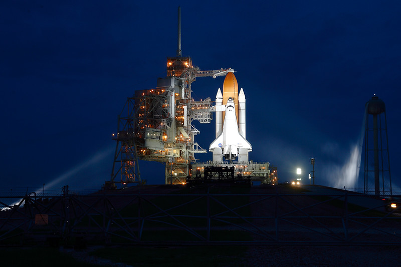 <i>Atlantis</i> on the launch pad later in the evening. The Sound Suppression Water System's tower periodically expels excess water, as seen here.
