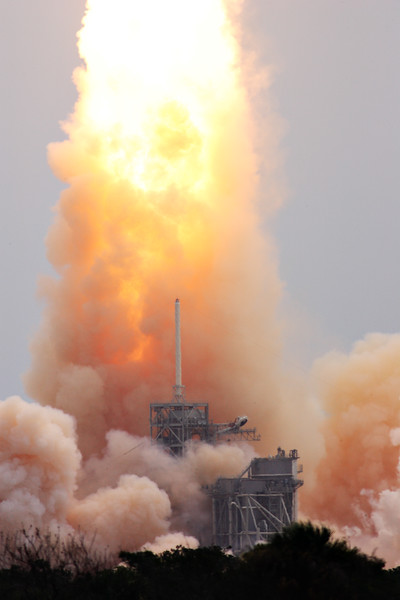 Flames from the Shuttle's Solid Rocket Boosters lick at  the launch pad as the vehicle lifts away.