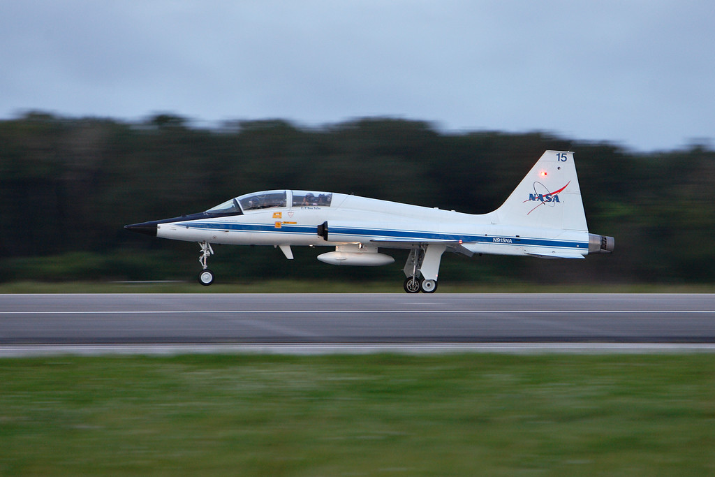 While the 747 waits at the end of the runway, the T-38 chase plane takes off next.<br /> <br /> NASA's T-38 fleet has been used by astronauts to fly between Johnson Space Center and Kennedy Space Center for shuttle missions.