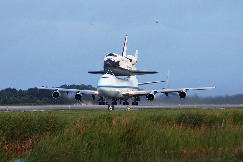 With the T-38 (left) and C-9 (right) formed up in the skies, the 747 begins its takeoff roll.