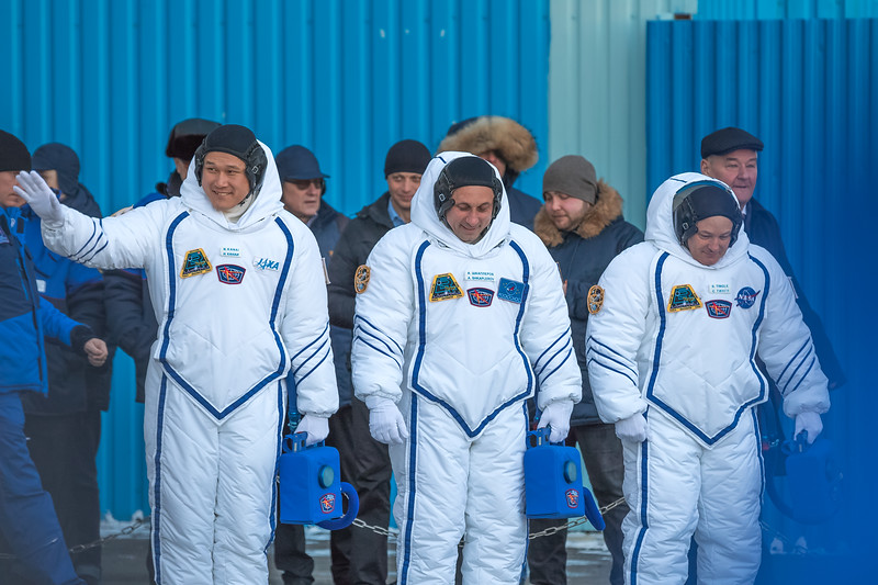 JAXA Flight engineer Norishige Kanai (left) waving to friends, family, and members of the media after donning his Sokol spacesuit at the Baikonur Cosmodrome in Kazakhstan on December 17th, 2017. (Photo Credit: Trevor Mahlmann)