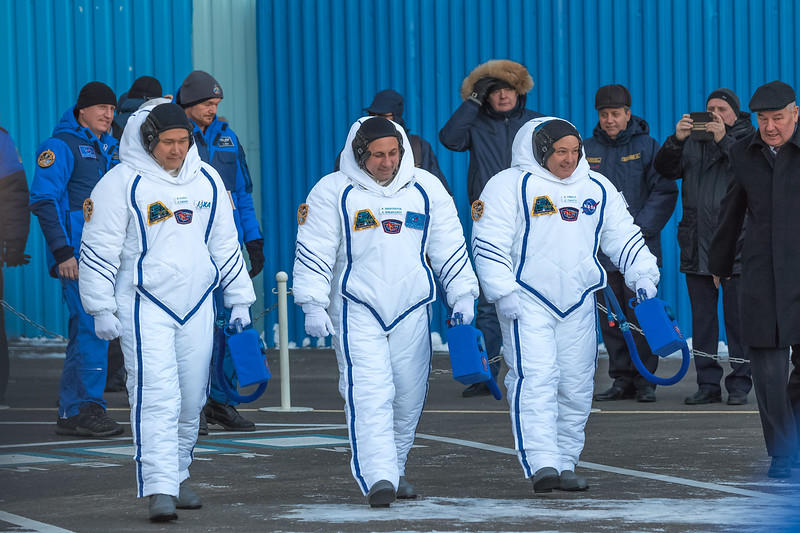 Flight Engineer Norishige Kanai (JAXA - left), Commander Anton Shkaplerov (Roscosmos - center), and Flight Engineer Scott Tingle (NASA - right) walking out of Building 254 at the Baikonur Cosmodrome after donning their Sokol spacesuits in Kazakhstan on December 17th, 2017. (Photo Credit: Trevor Mahlmann)