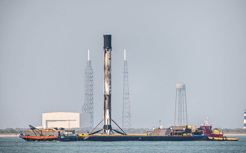 SpaceX's Falcon 9 standing (perspectively) between the towers of Blue Origin's LC-36 in Cape Canaveral as it rolls into port aboard the 'Of Course I Still Love You droneship.'