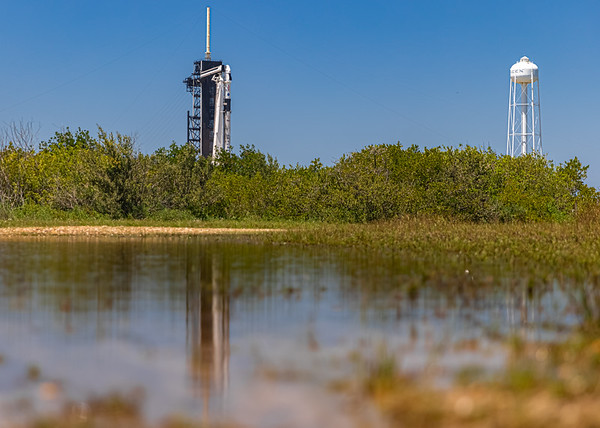 Crew Dragon, Falcon 9 and historic LC-39A reflected in a nearby puddle. One of Ars' sound-activated remote cameras is set to capture the Crew-2 mission lifting off from this vantage point.