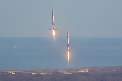 Two Falcon Heavy side boosters descending under rocket propulsion toward Cape Canaveral Air Force Station's LZ-1 and LZ-2. as they deploying their landing legs.  (Landing Zone 1 and Landing Zone 2)