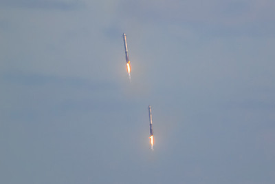 Two Falcon Heavy side boosters descending under rocket propulsion toward Cape Canaveral Air Force Station's LZ-1 and LZ-2. (Landing Zone 1 and Landing Zone 2)