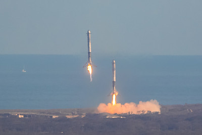 Two Falcon Heavy side boosters descending under rocket propulsion toward Cape Canaveral Air Force Station's LZ-1 and LZ-2 with fully down and locked landing legs.  (Landing Zone 1 and Landing Zone 2)