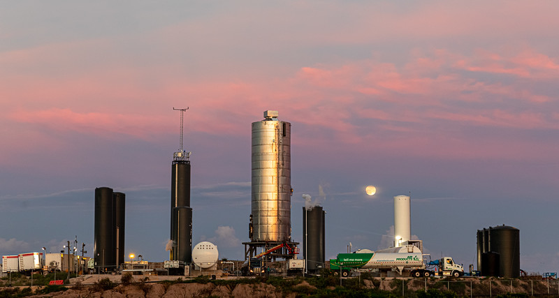 As a truckload of liquid oxygen arrives and the sun sets over SpaceX's South Texas launch site, the full moon rises in the background behind Starship SN5.
