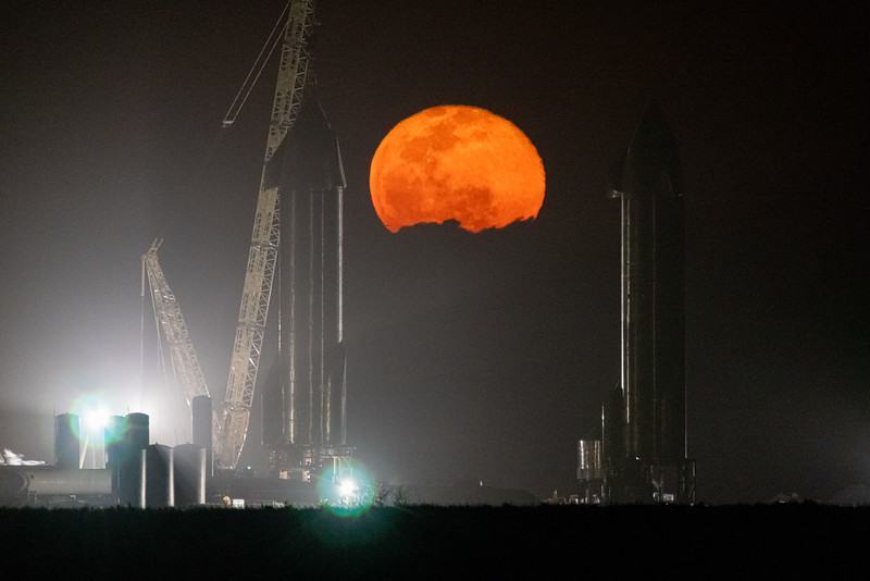 The full moon rises behind low clouds between SpaceX's Starship prototypes in Boca Chica Texas. (left - SN9, right - SN10)