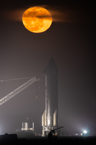 SpaceX's Starship SN9 prototype and the nearly-full Moon rising through a deck of clouds behind it.