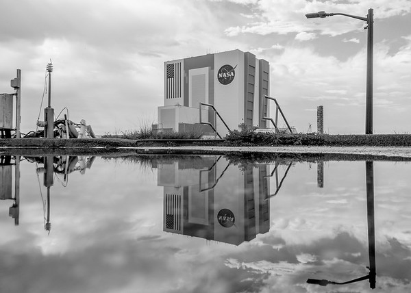The Vehicle Assembly Building reflected in a puddle following an afternoon storm at NASA's Kennedy Space Center.