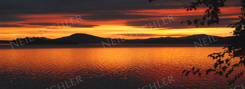 #758P  A fabulous sunset over Rangeley Lake in Rangeley, Maine, world-famous for its brook trout and land-locked salmon fishing.   This is a panoramic crop with a 2.75 x 1 ratio.