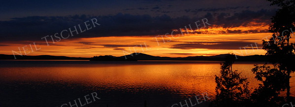 #757P  A fabulous sunset over Rangeley Lake in Rangeley, Maine, world-famous for its brook trout and land-locked salmon fishing.   This is a panoramic crop with a 2.75 x 1 ratio.