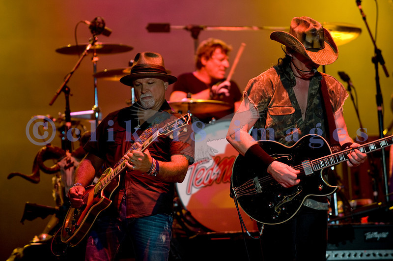 "Last minute replacement for Sunday's headliners Heart and Def Leppard, the Ted Nugent Band with its array of guitars as a backdrop showed that old rockers still rock. Derek St. Holmes, guitar and vocals; ""Wild"" Mick Brown, drums; Ted Nugent, guitar and vocals"