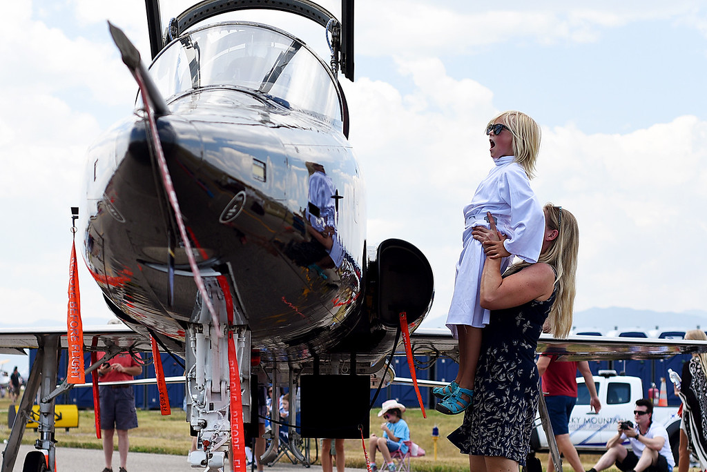 . Oliver Straus, 8, is hoisted up in the air by his mother, Emelie Straus, to get a better look of an Air Force jet cockpit during the Broomfield Air and Car Show held at the Rocky Mountain Metropolitan Airport on Saturday.  Kira Vos / Special to the Camera / August 4, 2018