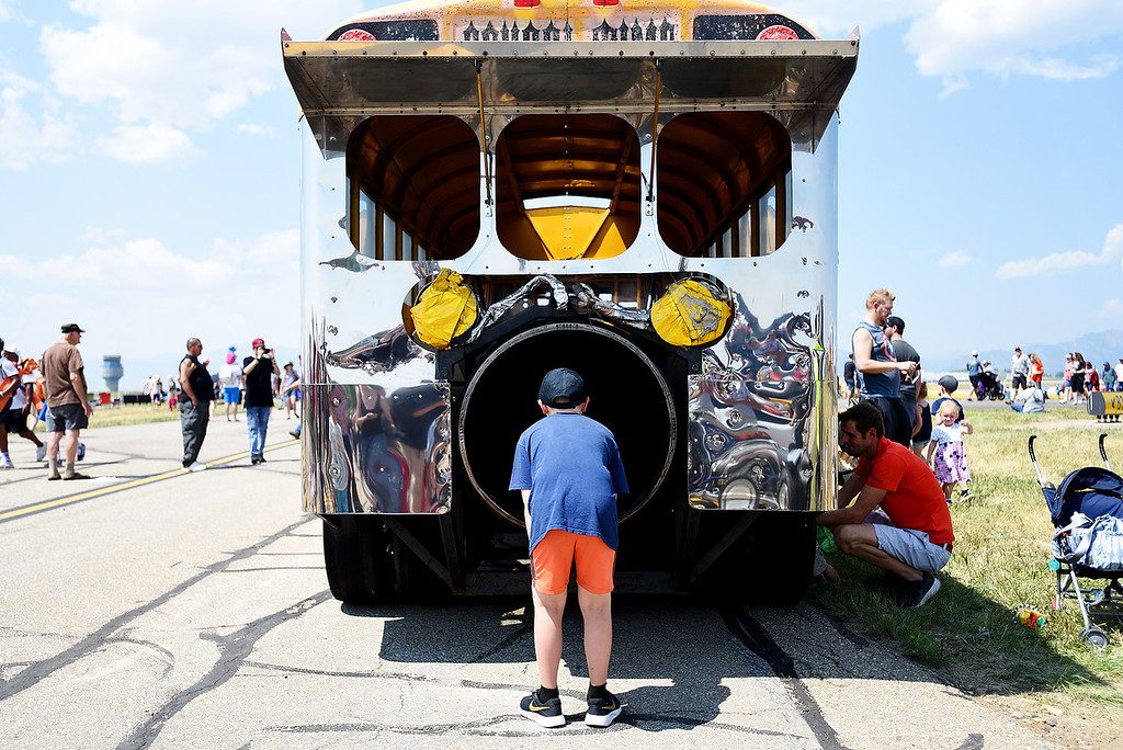 . Jason Brenckle, 9, stares down the exhaust pipe of a jet propelled school bus at the Broomfield Air and Car Show held at the Rocky Mountain Metropolitan Airport on Saturday.  Kira Vos / Special to the Camera / August 4, 2018