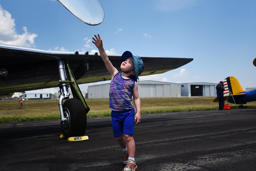 . Annika Schnur, 3, reaches for the propeller of a 1945 P-51D Mustang at the Broomfield Air and Car Show held at the Rocky Mountain Metropolitan Airport on Saturday.  Kira Vos / Special to the Camera / August 4, 2018