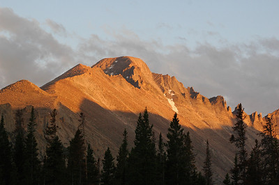 The bulk of mighty Long's Peak glows  with the day's last sunlight.  The rock formation known as The Keyboard of the Winds can be seen trailing off to the right.