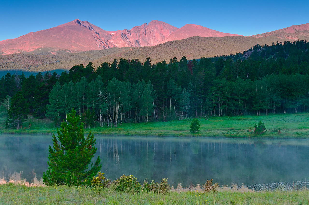 Rosy Dawn lights mighty Long's Peak as seen from Highway #7 as the last of the fog fades on the still waters of a pond.