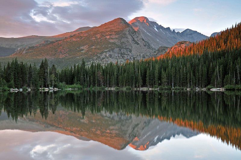 Bear Lake reflects the alpen glow from Long's Peak during a still morning in mid July bringing a feeling of peace.